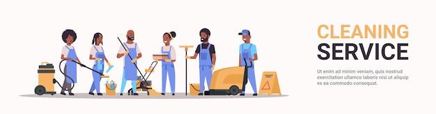 Reinigungspersonal in uniform, das zusammenarbeitet reinigungsdienstkonzept männliche hausmeisterinnen unter verwendung professioneller ausrüstung in voller länge horizontaler bannerkopierraum