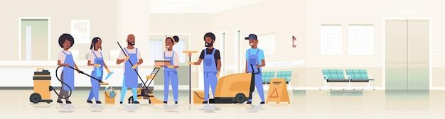 Reinigungsteam in uniform zusammenarbeiten reinigungsservice konzept hausmeister mit professionellen geräten klinik empfang krankenhaus korridor innenraum in voller länge horizontal