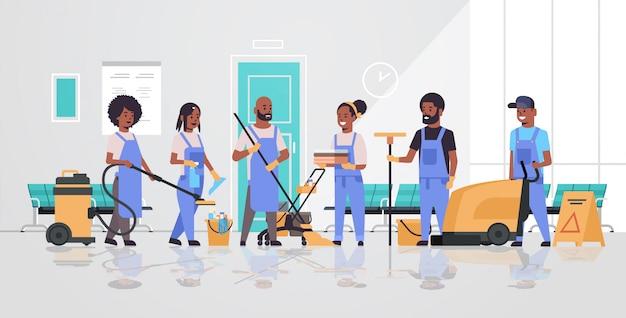 Reinigungsteam in uniform zusammenarbeiten reinigungsservice konzept hausmeister mit professioneller ausrüstung modernen krankenhaus korridor innenraum in voller länge horizontal