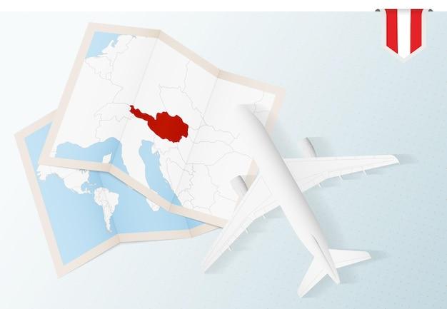 Reise nach österreich, draufsicht flugzeug mit karte und flagge von österreich.