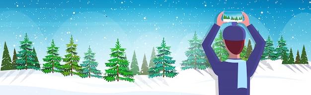 Reiseblogger, der smartphone-kamera verwendet, die verschneiten wald während des wanderns bloggt live-streaming fernweh-konzept winterlandschaft hintergrund horizontales porträt