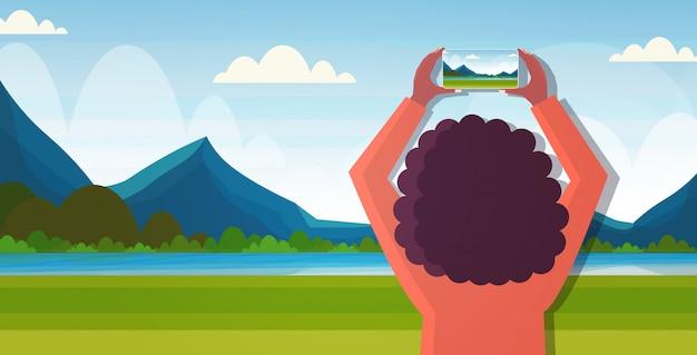 Reiseblogger unter verwendung der smartphone-kamera während der wanderfrau, die foto- oder video-blogging-live-streaming fernwehkonzeptgebirgslandschaftshintergrund-horizontales porträt nimmt