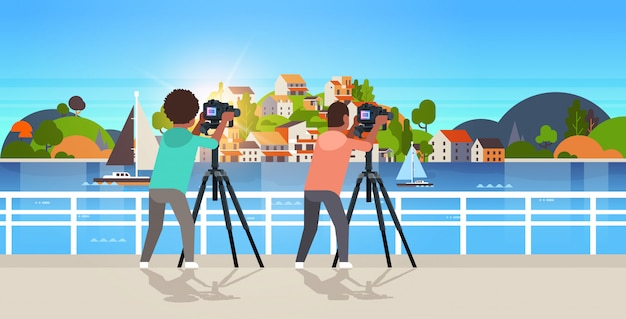 Reisefotografen, die naturbild von bergstadt-inselmenschen unter verwendung der dslr-kamera auf dem horizontalen stativlandschaftshintergrund machen