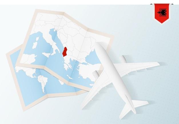 Reisen sie nach albanien, draufsichtflugzeug mit karte und flagge albaniens.