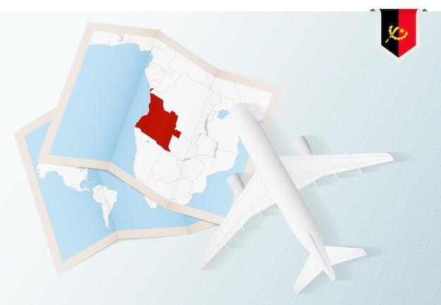 Reisen sie nach angola, draufsichtflugzeug mit karte und flagge von angola.