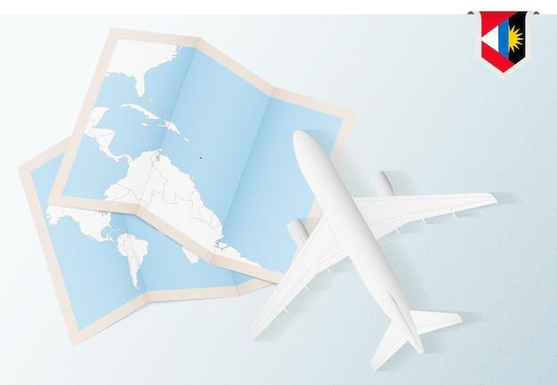 Reisen sie nach antigua und barbuda, draufsichtflugzeug mit karte und flagge von antigua und barbuda.