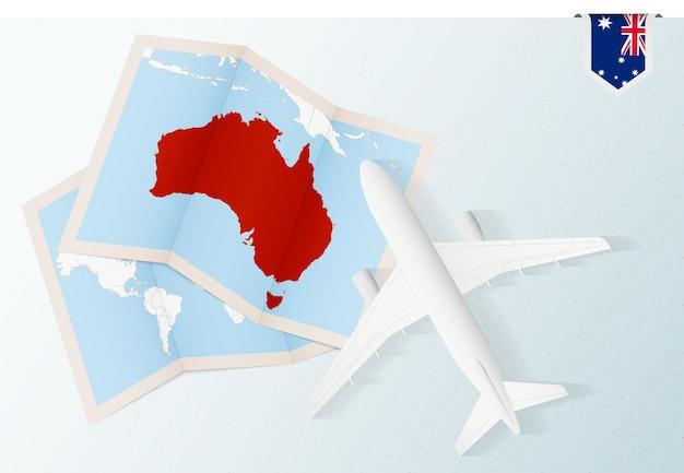 Reisen sie nach australien, draufsichtflugzeug mit karte und flagge von australien.