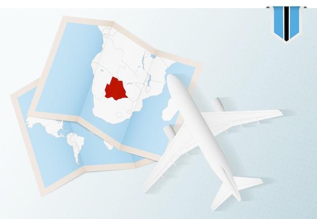 Reisen sie nach botswana, draufsichtflugzeug mit karte und flagge von botswana.