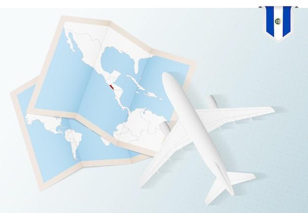 Reisen sie nach el salvador, draufsichtflugzeug mit karte und flagge von el salvador.