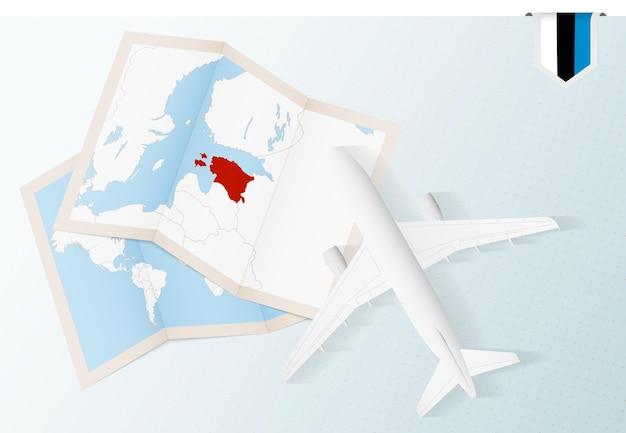 Reisen sie nach estland, draufsichtflugzeug mit karte und flagge von estland.