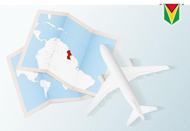 Reisen sie nach guyana, draufsichtflugzeug mit karte und flagge von guyana.