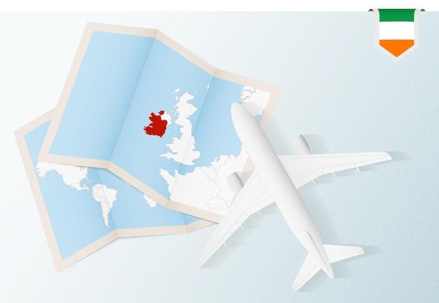 Reisen sie nach irland, draufsichtflugzeug mit karte und flagge von irland.