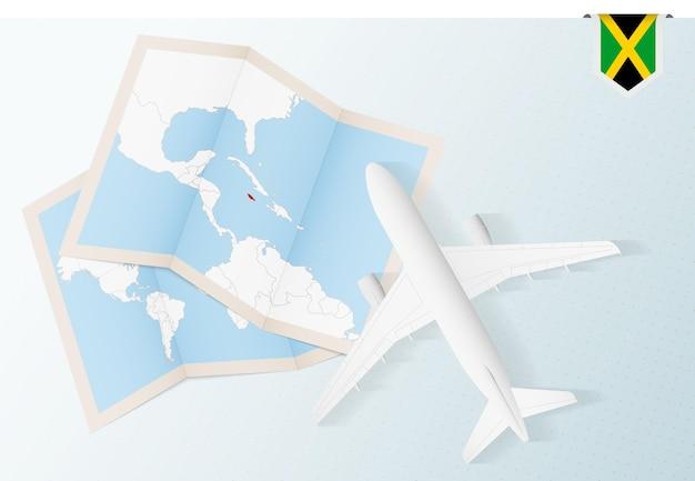 Reisen sie nach jamaika, draufsichtflugzeug mit karte und flagge von jamaika.
