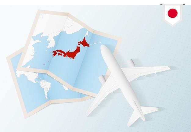 Reisen sie nach japan, draufsichtflugzeug mit karte und flagge von japan.