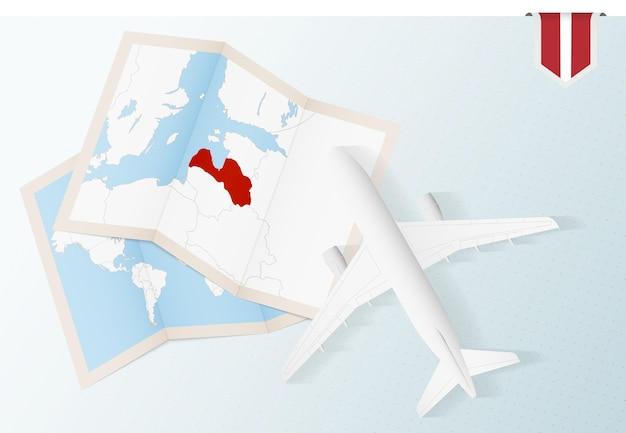 Reisen sie nach lettland, draufsichtflugzeug mit karte und flagge lettlands.