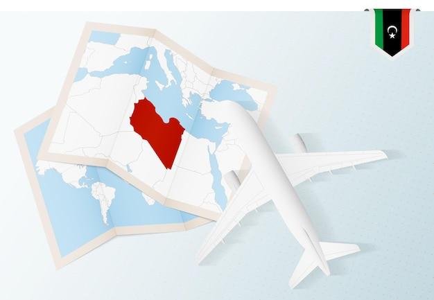 Reisen sie nach libyen, flugzeug von oben mit karte und flagge von libyen.