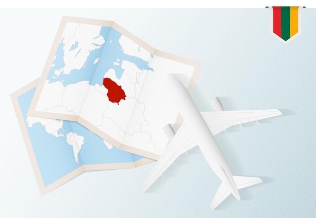 Reisen sie nach litauen, draufsichtflugzeug mit karte und flagge litauens.