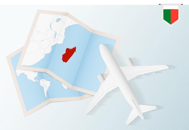 Reisen sie nach madagaskar, draufsichtflugzeug mit karte und flagge von madagaskar.