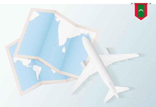 Reisen sie nach malediven, draufsichtflugzeug mit karte und flagge der malediven.