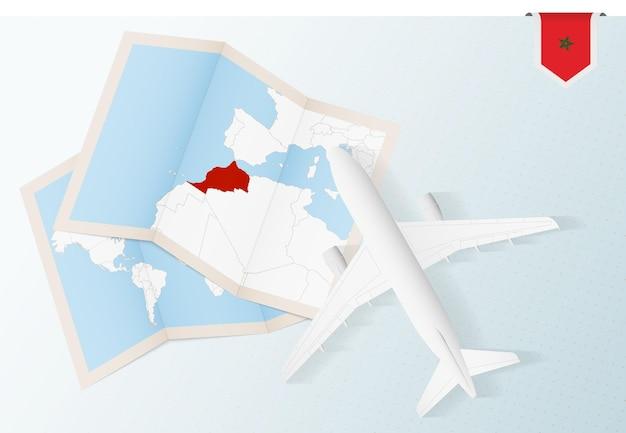 Reisen sie nach marokko, draufsichtflugzeug mit karte und flagge von marokko.