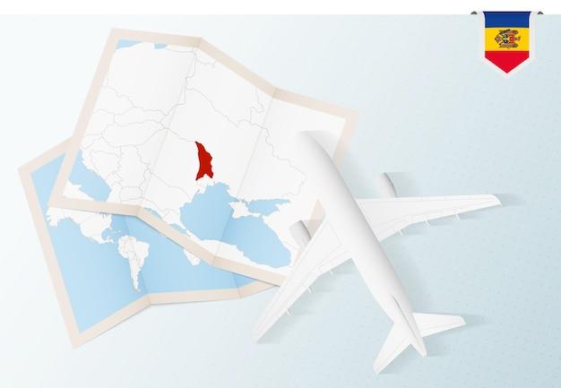 Reisen sie nach moldawien, draufsichtflugzeug mit karte und flagge von moldawien.