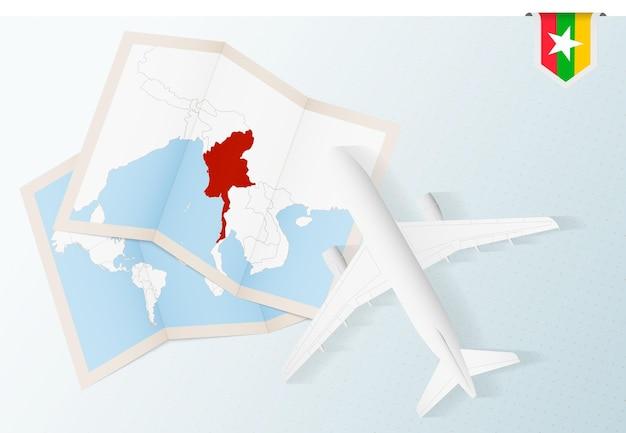 Reisen sie nach myanmar, draufsichtflugzeug mit karte und flagge von myanmar.
