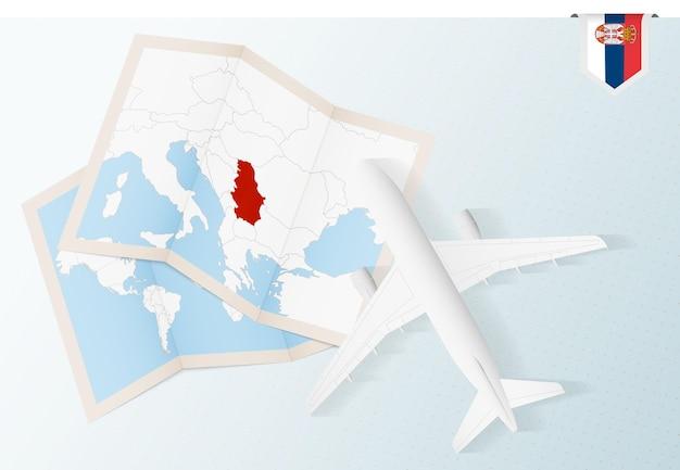 Reisen sie nach serbien, draufsichtflugzeug mit karte und flagge von serbien.