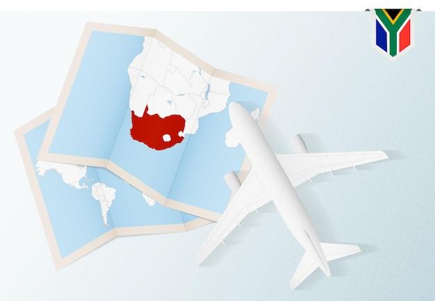 Reisen sie nach südafrika, draufsichtflugzeug mit karte und flagge von südafrika.