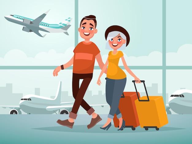 Reisende junge leute. mann und frau mit gepäck gehen in das flughafengebäude.