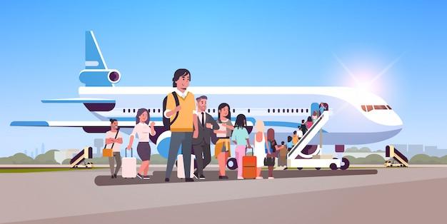 Reisende mit einer warteschlange für das stehen des gepäcks gehen zu flugzeugpassagieren, die die leiter erklimmen, um an bord des flugzeugkonzeptes flache horizontale zu steigen