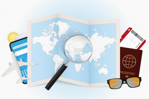 Reiseziel bulgarien, tourismusmodell mit reiseausrüstung und weltkarte mit lupe auf bulgarien.