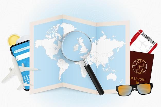 Reiseziel irland, tourismusmodell mit reiseausrüstung und weltkarte mit lupe auf irland.