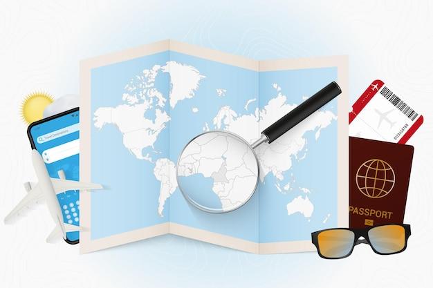 Reiseziel kamerun, tourismusmodell mit reiseausrüstung und weltkarte mit lupe auf einem kamerun.