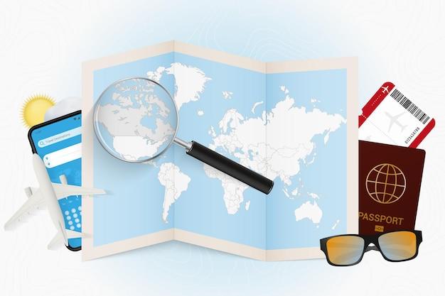 Reiseziel kanada, tourismusmodell mit reiseausrüstung und weltkarte mit lupe auf kanada.