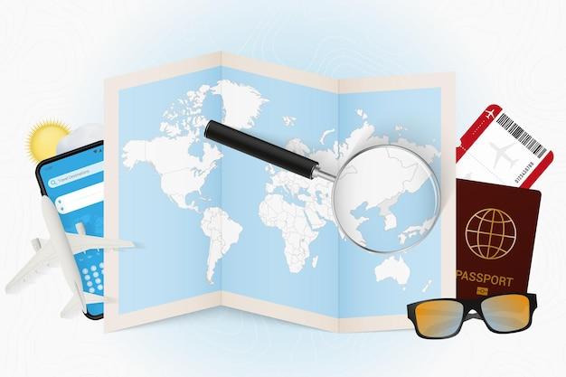 Reiseziel nordkorea, tourismusmodell mit reiseausrüstung und weltkarte mit lupe auf nordkorea.