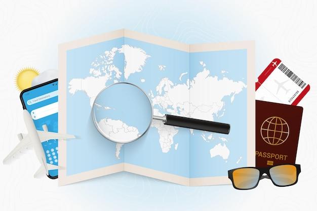 Reiseziel st. vincent und die grenadinen, tourismusmodell mit reiseausrüstung und weltkarte mit lupe auf einem st. vincent und die grenadinen.