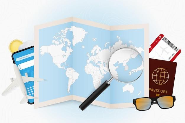 Reiseziel südkorea, tourismusmodell mit reiseausrüstung und weltkarte mit lupe auf südkorea.