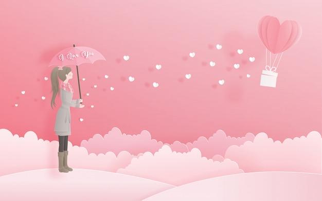 Reizendes mädchen, das einen regenschirm betrachtet herzballon, valentinstag und karte hält