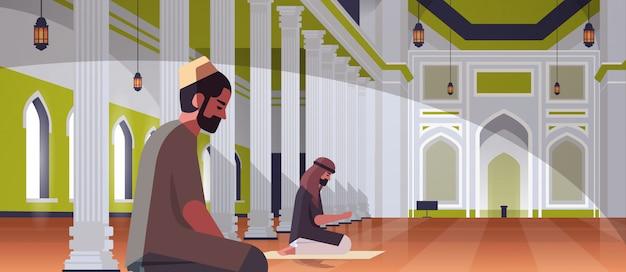 Religiöses muslimisches männerpaar kniend und betend innerhalb des nabawi-moscheegebäudes ramadan kareem heiliger monat religion konzept in voller länge horizontal