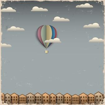 Retro heißluftballon und stadt aus papier