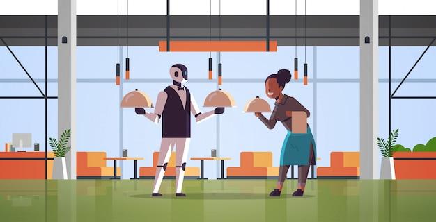 Roboterkellner mit der kellnerin, die behälter mit tellerroboter gegen den menschen zusammen steht technologie-lebensmittelumhüllungskonzept der künstlichen intelligenz das moderne horizontale restaurantinnere in voller länge
