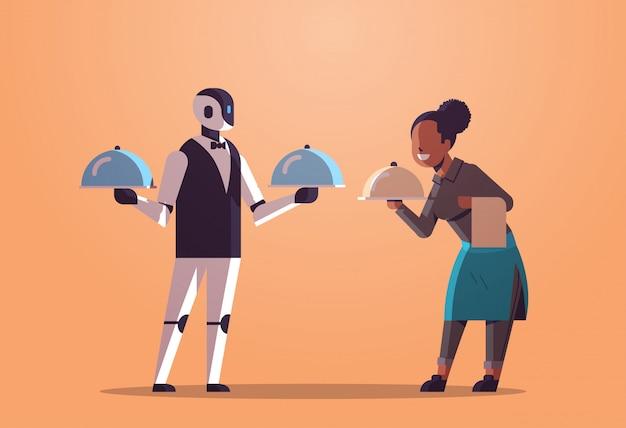 Roboterkellner mit der kellnerin, die behälter mit tellerroboter gegen menschliche restaurantarbeitskräfte im einheitlichen technologielebensmittelumhüllungskonzept der künstlichen intelligenz flach in voller länge horizontal hält