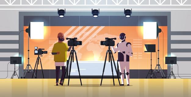 Roboteroperator mit dem kameramann, der videokamera auf stativroboter gegen den menschen zusammen steht, sendend das technologiekonzeptnachrichtenstudio des künstlichen intelligenzinnenraums in voller länge horizontal