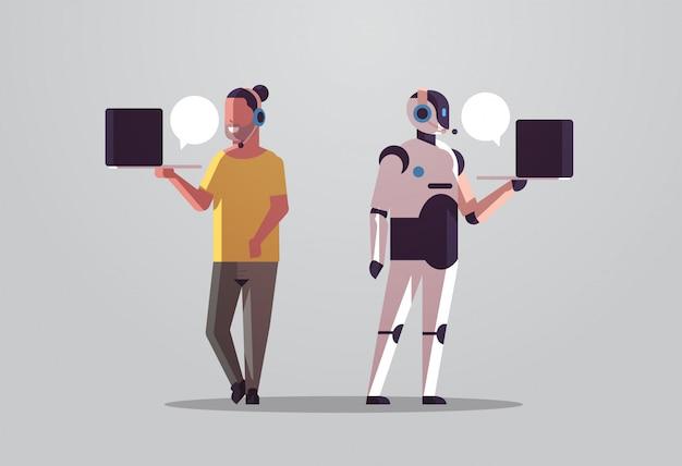 Roboteroperator mit dem mannberater, der laptopchatblasen-kundenunterstützungsroboter gegen menschliches stehendes zusammen horizontales call-center-technologiekonzept der künstlichen intelligenz flach in voller länge verwendet