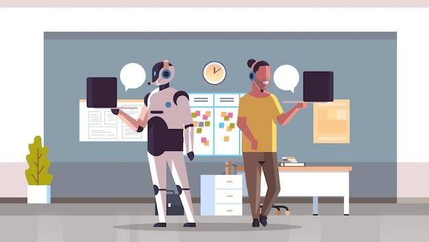 Roboteroperator mit dem mannberater, der laptopchatblasen-kundenunterstützungsroboter gegen menschliches stehendes zusammen horizontales innenkonzept der künstlichen intelligenz des call-center-büros verwendet