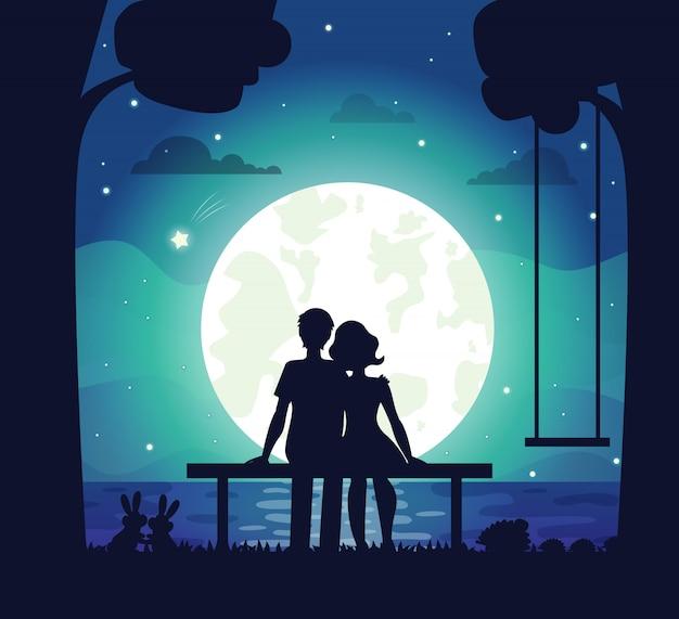 Romantische paare, die auf küste unter mondschein sitzen