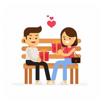 Romantisches paar, das auf einer bank sitzt und sich geschenke zum valentinstag schenkt