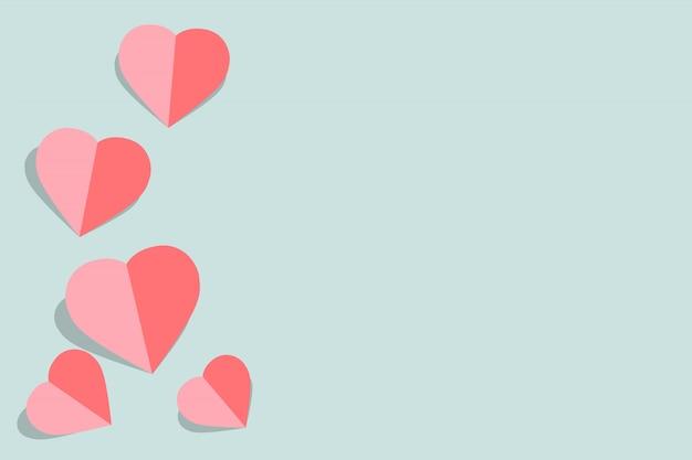 Rosa papierherzen valentinsgrußtageskarte auf pastellblau