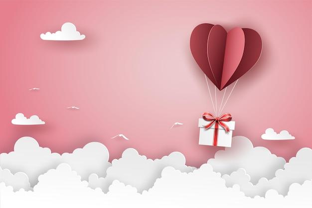 Roter origami-heißluftballon in herzform mit geschenkbox, die auf dem himmel über der wolke fliegt.