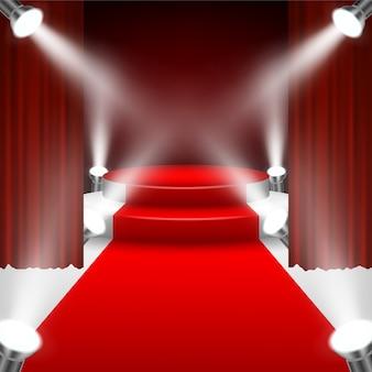 Roter teppich zur podiumsbühne mit scheinwerfern und rotem vorhang